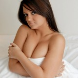 Brooke covers her huge breasts with just the bed sheets